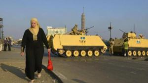 A woman walks past Egyptian army tanks in downtown Cairo (photo: dpa)