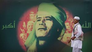 Libyan man passes billboard of Gaddafi′s face and the Arabic tag ″God is great″, Tripoli 2009 (source: AP/Ben Curtis)