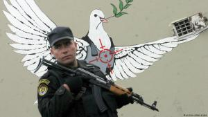 Armed Palestinian soldier stands in front of Banksy peace dove graffito in Bethlehem, West Bank (photo: picture-alliance/dpa)