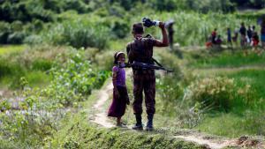 Bangladesh border guard at Cox's Bazar prevents Rohingya girl from crossing border (photo: Reuters/M. Ponir Hossain)