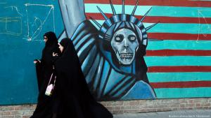 Two Iranian women walk past graffiti (skull atop the Statue of Liberty) on the former U.S. Embassy in Tehran (photo: picture-alliance/dpa)