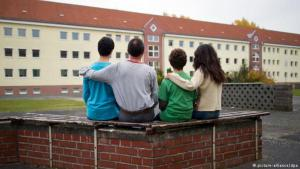 Syrian asylum-seekers in front of a German refugee hostel (photo: picture-alliance/dpa)