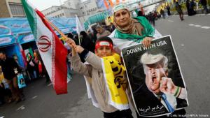 An Iranian woman holds a placard showing a caricature of Donald Trump during a rally marking the anniversary of the Islamic Revolution in February 2017. Millions marched in response to the new U.S. administrationn and a rejection of threatening language (photo: Getty Images/AFP/A. Kenare)