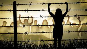 A woman stands at a barbed wire fence, in the background on the other side stands a crowd of people (photo: Benjamin Haas/Fotolia)