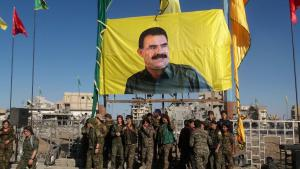 Troops belonging to the Syrian Democratic Forces pose in front of a banner bearing the likeness of Abdullah Ocalan, leader of the PKK, in Raqqa on 19 October 2017 (photo: AFP/Getty Images)