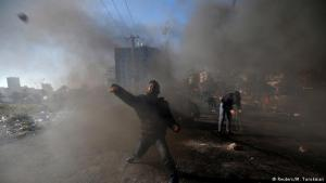 """Clashes with police: a Palestinian protester hurls stones toward Israeli police during clashes near the Jewish settlement of Beit Al, close to the West Bank city of Ramallah. Palestinians called for a """"day of rage"""" in response to U.S. President Donald Trump′s decision to recognise Jerusalem as Israel's capital. At least two protesters were killed on Friday during clashes with security forces"""
