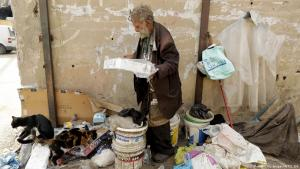 """Georges Gerges, 90, nicknamed """"Captain' feeds his cats at the corner of a street in the industrial zone of Dora on the northern outskirts of Beirut on 8 November 2017 (photo: Getty Images/AFP/J. Eid)"""