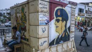 A man sits next to a mural of Abdul Fattah al-Sisi in Sharm al-Sheikh (photo: Khaled Desouki/AFP/Getty Images)