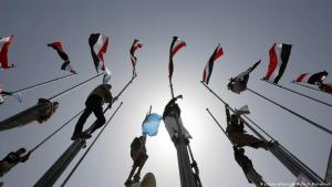 In this photo dated 26.03.2016, supporters of Yemen's deceased former President Ali Abdullah Saleh and allies of Shia Houthi rebels, climb flag poles in Sanaa during a rally to mark the first anniversary of the Saudi-led military campaign against them (photo: picture-alliance/AP Photo/H. Mohammed)
