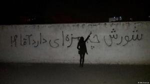 """Iranian woman in front of graffiti bearing the message """"And how do you like the protests, Sir?"""", the ʹSirʹ in this instance being Ayatollah Khamenei (photo: DW)"""