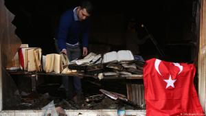 A Koca Sinan Camii mosque congregation member inspects damage to the mosque and Korans the day after a fire there the previous night, as a Turkish flag hangs nearby, on 11 March 2018 in Berlin, Germany (photo: Getty Images/Adam Berry)