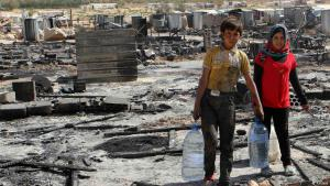 This archive photo dated 09.08.2014 shows Syrian refugee children carry water bottles as they walk amid damage and the remains of tents for Syrian refugees that were burnt in the fighting between Lebanese army soldiers and Islamist militants in the Sunni Muslim border town of Arsal, in Lebanon's eastern Bekaa Valley (photo: Reuters/Ahmad Shalha)