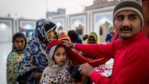 Pilgrims receive a blessing at the shrine of Lal Shahbaz Qalandar (photo: Philipp Breu)