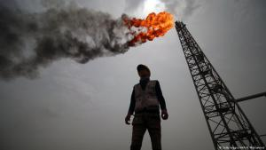 Oil worker standing in front of a derrick in Iraq (photo: Haidar Mohammed Ali/AFP/Getty Images)