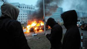 Young people watch a burning car during a riot in a Paris suburb (photo: picture-alliance/abaca)