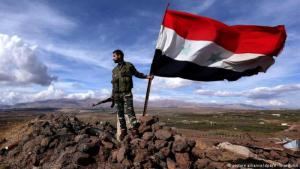 A Syrian government army soldier with a national flag (photo: picture-alliance/dpa/V. Sharifulin)