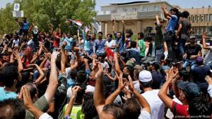 Iraqi citizens shout slogans as they gather to protest against government due to lack of basic services and frequent power outages in front of the governor's building in Iraqʹs oil-rich Basra province on 15 July 2018 (photo: picture-alliance/AP Photo)