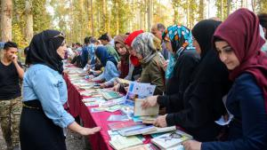"Iraqi youth and elders browse a book display at a festival titled ""I am Iraqi.. I read"" at a park in Mosul on Saturday in the first event of its kind after the city was retaken from IS militants (source: Rudaw English; Twitter)"