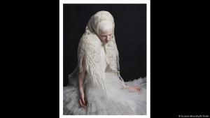 A woman wearing a lacey white headscarf and tulle skirt looks downwards (photo: Susanne Bisovsky/B. Preiml)