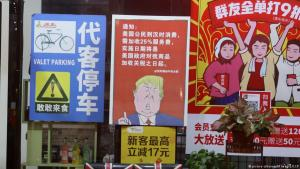 A poster depicting U.S. president Donald Trump, stating that all U.S. customers will be charged 25 percent more than others starting from the day President Trump started the trade war against China, is displayed outside a restaurant in Guangzhou in south China's Guangdong province on 13 August, 2018 (photo: picture-alliance/AP Images/CCP)