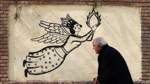 Man passing a mural on Si Tir Street in Tehran, a famous boulevard in the Iranian capital (photo: Tasnim)