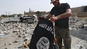 Militia supporter in Syria burns an IS flag in Raqqa (photo: picture-alliance/AP/dpa)
