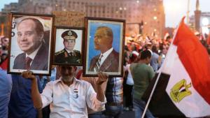 During a demonstration on Tahrir Square in Cairo on 3 June 2014, a man holds up images of the Egyptian President Abdul Fattah al-Sisi and former president Gamal Abdel Nasser (photo: Reuters/Asmaa Waguih)