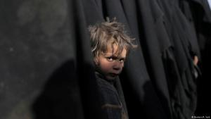 A boy stands in a line of niqab-wearing women near Baghouz, Syria, 05.03.2019 (photo: Reuters/R. Said)