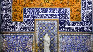 A woman stands in Sheikh Lotfallah mosque in Isfahan, Iran. This mosque is a true masterpiece of architecture and refinement. It was built between 1602 and 1619 during the Safavid Empire. The decorative detail is breathtaking