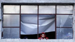 A Syrian child displaced from eastern Ghouta with his family watches from the window of their shelter in the village of Horjelli in the Damascus countryside, Syria, 13 April 2018 (photo: picture-alliance/AP Photo/H. Ammar)