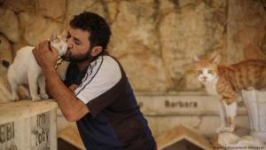 "Helping animals in need: Mohammed Alaa al-Jaleel, also known as ""The Cat Man of Aleppo"", helps a cat from the ruins of a bombed out area in Khan Shaykhun, where he searches for live cats to bring them to his ""Ernesto's Cat Sanctuary"