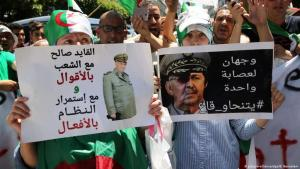 "Demonstrators protest on the streets of Algiers against army commander Gaid Saleh on 20 November 2019. Placards read ""He says he is for the protesters, but in fact he intends to preserve the status quo"", ""They all must go: Gaid Saleh – Two faces of the same regime"" (photo: picture-alliance/dpa/B. Bensalem)"