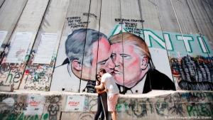 A couple hug in front of a wall in Jerusalem that depicts Donald Trump and Benjamin Netanyahu kissing each other (photo: Getty Images/AFP/M.A. Shaers)