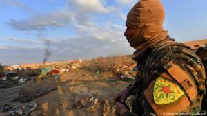 Member of the YPG observes as IS positions near Baghouz come under attack in Syria (photo: Getty Images/AFP/G. Cacace)