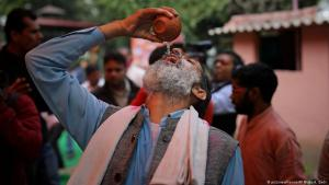 An Indian Hindu drinks cow urine during an event organised by an event by a religious group promoting cow urine consumption as a cure for the new coronavirus in New Delhi, India (photo: picture-alliance/AP Photo)