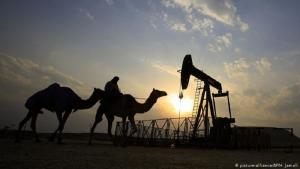 A man rides a camel through a desert oil field (photo: picture-alliance/AP/H. Jamali)