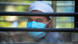 A man wearing a protective face mask looks out the window of a bus in India (photo: Getty Images/AFP/S. Hussain)