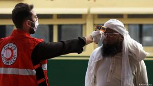 A member of the Red Crescent Pakistan takes a man's temperature (photo: Reuters/F. Aziz)