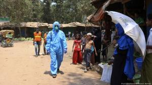 A health worker from an aid organistation walks through Kutapalong refugee camp in Cox's Bazar wearing a hazmat suit (photo: picture-alliance/AP Photo/S. Rahman)