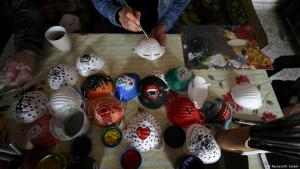 Palestinian artists decorating protective masks in Gaza (photo: Reuters/M. Salem)