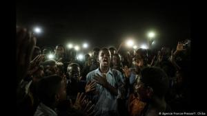 """Straight Voice"", Khartoum, Sudan: a young man recites a poem, holding his left hand to his chest. He is surrounded by demonstrators who light him up with their cell phones. The jury chose the picture by the Japanese artist Yasuyoshi Chiba because it provides inspiration to the viewer in uncertain times. It also won the category ""General News, Single Image"" (photo: AFP/Y. Chiba)"