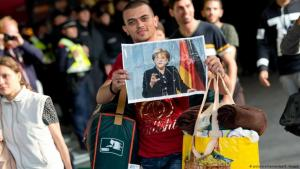 Refugee arriving in Germany grasping a crumpled picture of Angela Merkel (picture-alliance/dpa/S. Hoppe)