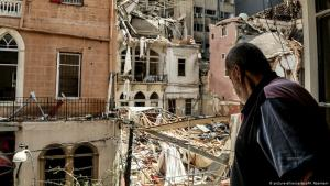 A man looks out of the window of his damaged apartment in downtown Beirut at the destruction caused by the explosion in Beirut Port, 14.08.2020 (photo: picture-alliance/dpa/M. Naamani)