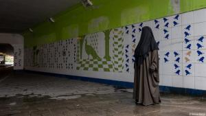 A woman stands in an empty tunnel in Amsterdam wearing a black burka (photo: Sanne Derks)