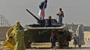 Children climb on an abandoned Soviet tank in Mazar-e-Sharif (photo: AP)