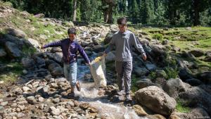 Majid Magray, 12, and Waseem Ahmed, 16, collecting rubbish left behind by tourists near a waterfall in Pahalgam, Jammu and Kashmir (photo: Furkan Khan)