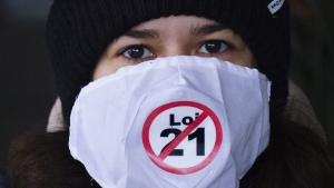 "A demonstrator displays her opinion outside the courthouse on the first day of the constitutional challenge to Bill 21, which bans public workers in positions of ""authority"" from wearing religious symbols, before the Quebec Superior Court in Montreal on 2 November 2020 (photo: THE CANADIAN PRESS/Paul Chiasson)"