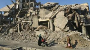 Photo from Abood Hamam shows a woman pushing a stroller through rubble