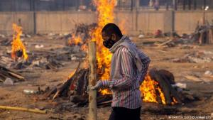 A man walks past burning funeral pyres of people who died of COVID-19 at a crematorium ground in New Delhi