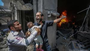 Paramedic and man with baby in rubble, Gaza (photo: Mohammed Talatene/dpa/pciture-alliance)